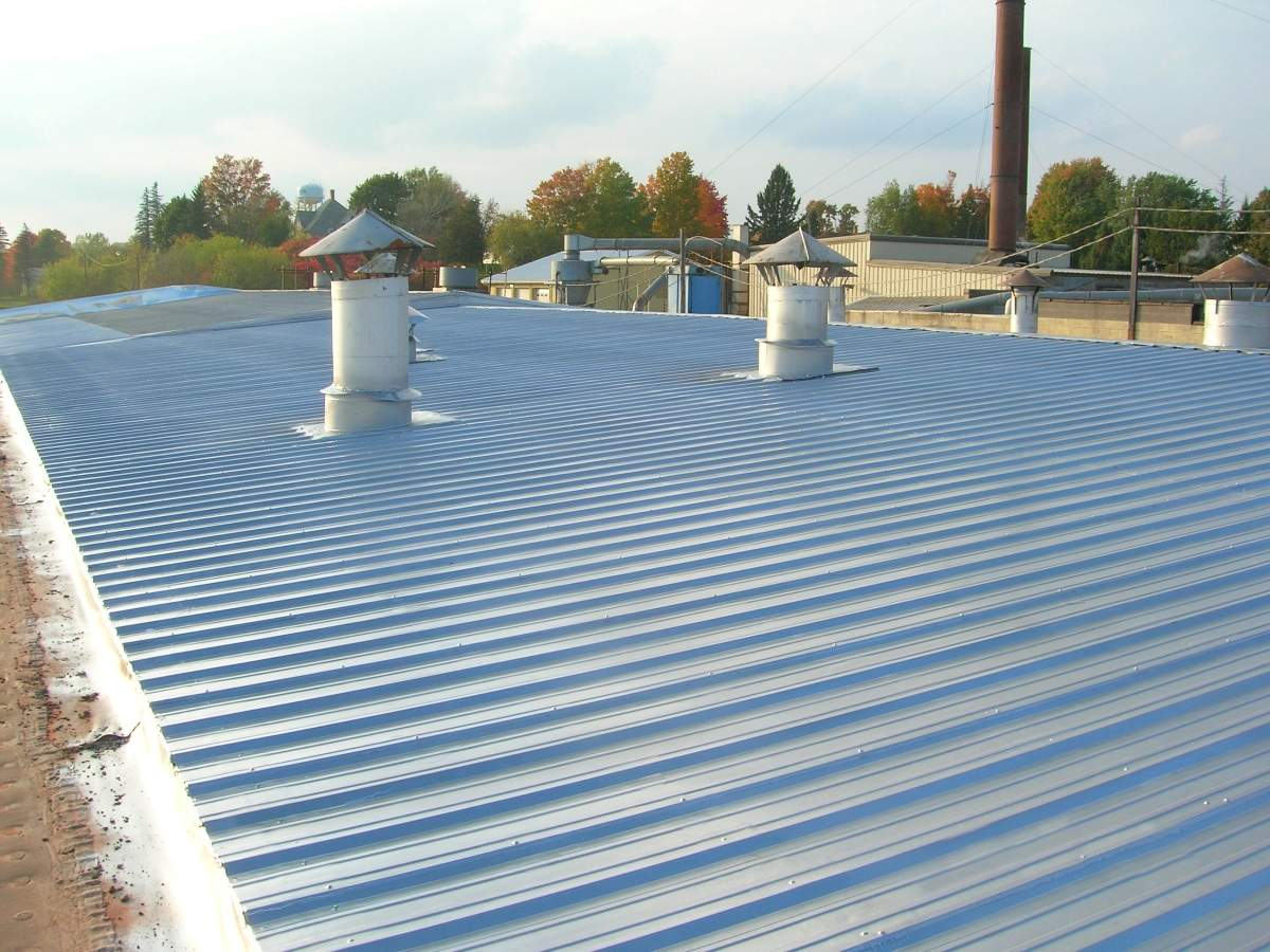Coating metal roof seams to prevent leaks.JPG