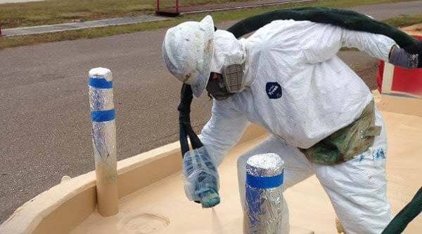 technician spraying cracked concrete containment area